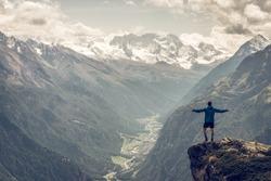 Man standing on a mountain rock panorama
