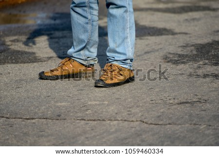 Man standing on a road wearing stylish shoe & jeans wears isolated unique stock photo #1059460334