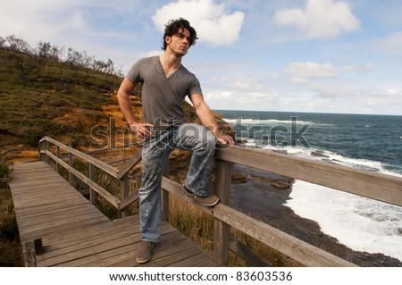 Man standing on a walk way overlooking the ocean