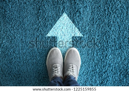 Man standing on carpet with arrow pointing in one direction. Concept of choice Сток-фото ©