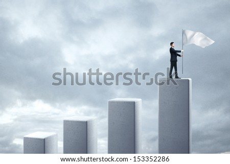 man standing on column and holding flag
