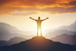 Man standing on edge of mountain feeling victorious with arms up in the air. Success, life goals, achievement concept.