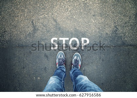 Man standing on grunge asphalt city street with written stop sign on the floor, point of view perspective. #627916586