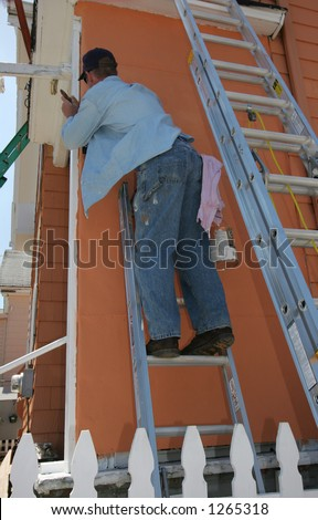 man standing on ladder painting outside of house