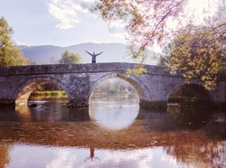 Man standing on old bridge by the river with ancient arch