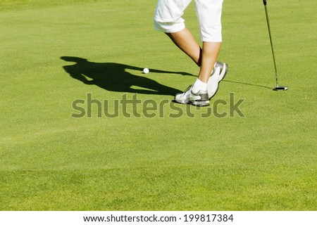 Man standing on putting green, low section