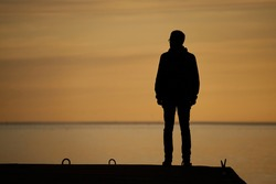 man standing on rock looking straight. Nature and beauty concept. Orange sundown. silhouette at sunset