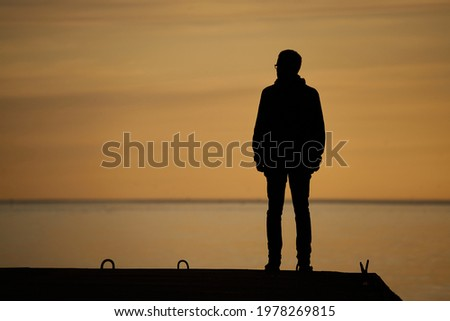 man standing on rock looking straight. Nature and beauty concept. Orange sundown. silhouette at sunset Foto stock ©