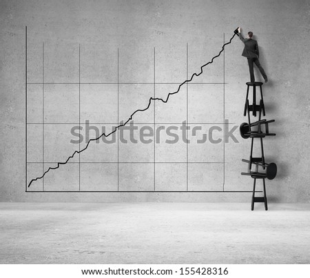 man standing on stool and drawing arrow