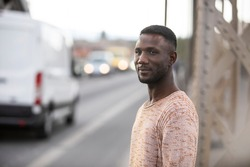 Man standing on street with cars in background. Shallow depth of field. Focus on foreground. Side view. Medium shot.