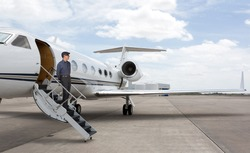 Man standing on the stars of a private jet wearing a hat.