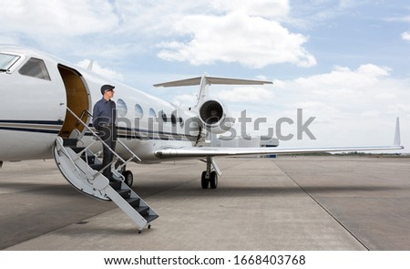 Man standing on the stars of a private jet wearing a hat. Stock fotó ©