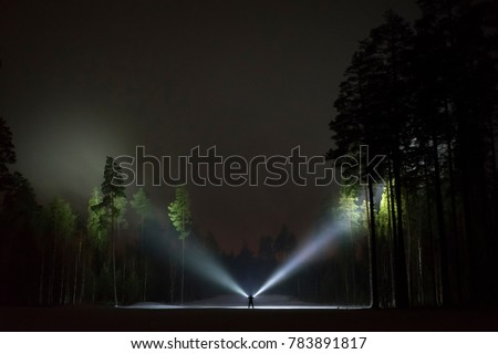 Man standing outdoor at night in forest shining with two flashlights up in dark sky and at trees. Nice strong light beams. beautiful abstract photo. Calm, peaceful and mystical image.