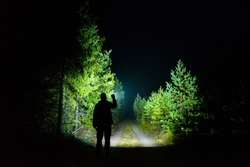 Man standing outdoor at rainy foggy night shining with flashlight. Mystical and abstract photo of Swedish nature and landscape.