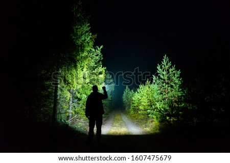 Man standing outdoor at rainy foggy night shining with flashlight. Mystical and abstract photo of Swedish nature and landscape. Foto stock ©