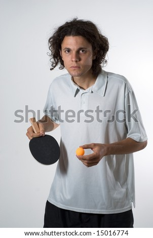 Man standing up holding a ping pong ball and a paddle. He has a serious expression on his face. Vertically framed photograph
