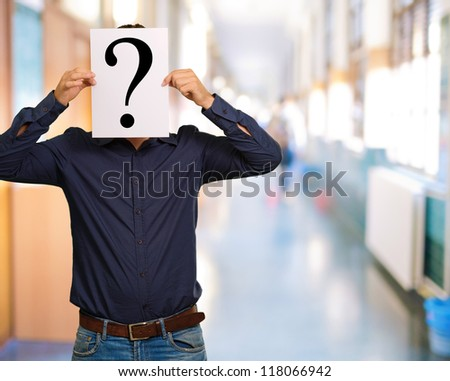 Man standing with a question mark board, outdoor