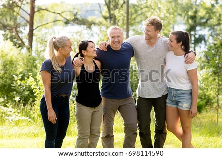 Man Standing With Arms Around Friends In Forest #698114590