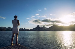 Man standing with arms crossed at sunset in front of Rio de Janeiro Brazil skyline at Lagoa lagoon