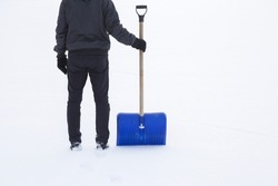 Man standing with blue shovel and he is ready for snow cleaning. Winter routine concept.