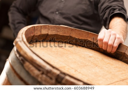 Photo of Man standing with his hand on a wooden oak barrel or cask in a winery, distillery or brewery for maturing the alcohol in a conceptual close up image
