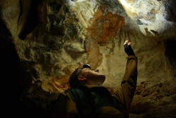 Man stands and pulls his hand up in a karst cave inside the Mangup plateau in the Crimea, near the city of Bakhchisarai. A man with backpack is dressed in a brown windbreaker. Head torch on.