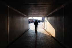 man stands at the end of a dark tunnel