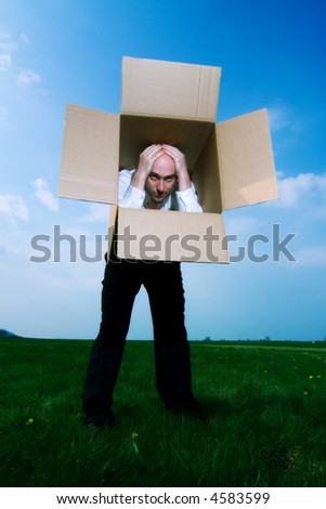Man stands holding his hands on top of his head.  His torso is covered by a cardboard box and he is looking out from the top of the open box.  The background is green grass and blue sky.