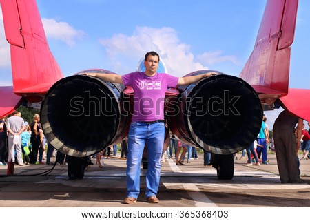 Man stands near nozzle of military aircraft on land during airshow at summer day