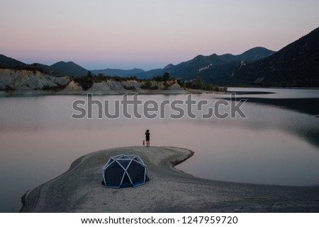 Man stands next to camping tent on lake or seaside beach, makes inspirational photo on smartphone of sunset light. Best friend, trail adventure dog or puppy next to him enjoy outdoors