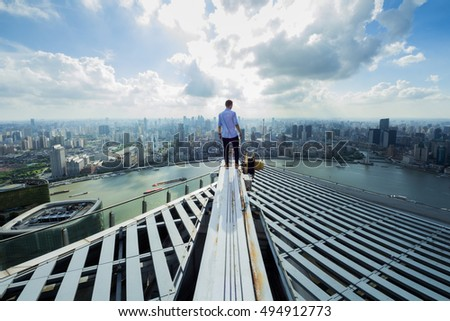 Man stands on roof of skyscraper in sunny Shanghai and looks at river, back view