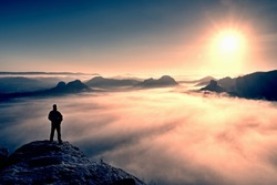 Man stands on the peak of sandstone rock in national park Saxony Switzerland and watching to Sun. Beautiful moment the miracle of nature. Misty valley. Man hike.Person silhouette stand.Foggy mountains