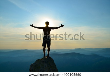 man stands on top of a mountain with open hands.