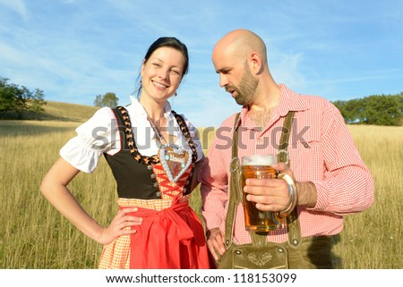man staring at the decollete of a happy woman in traditional bavarian garbs