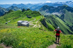 Man starting a trail run descent in Swiss Alps and panorama of mountains during summertime in Switzerland Europe