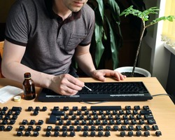 Man stays at home and thorough cleans the disassembled keyboard. Alcohol disinfection of the surface and inside
