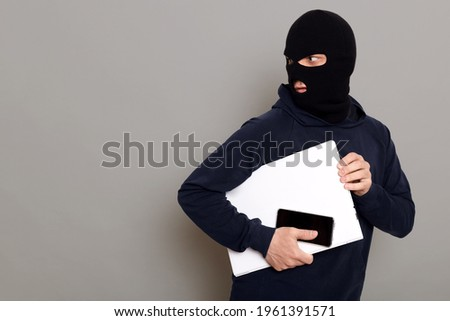 Man steals laptop and phone, runs away and turns back, being of persecution, wears robber mask and black turtleneck, advertising space, isolated over gray background. Сток-фото ©
