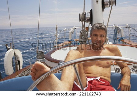 Man steering sailboat with foot