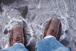 Man steps on frozen puddle with thin ice.