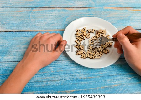 Man stirs wooden letters with a fork on a plate, choosing between food and knowledge. Carnal joys or spiritual truths Сток-фото ©