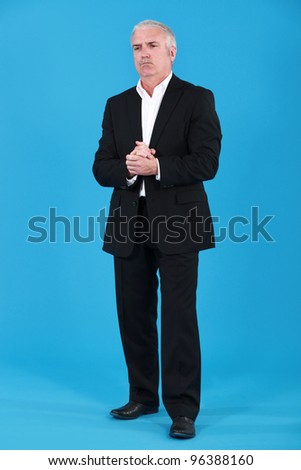 Man stood with hands clasped
