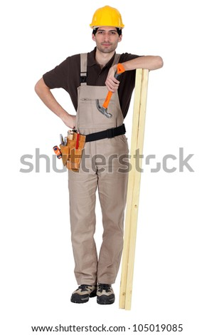 Man stood with plank of wood and hammer