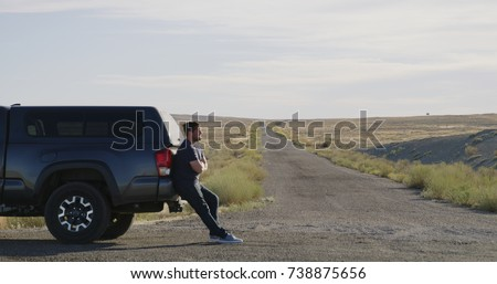 man stranded next to truck in middle of desert