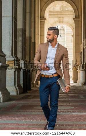 Man Street Fashion.Young East Indian American Businessman traveling, working in New York City, wearing brown blazer, blue jean, holding laptop computer, cell phone, walking on vintage narrow street.