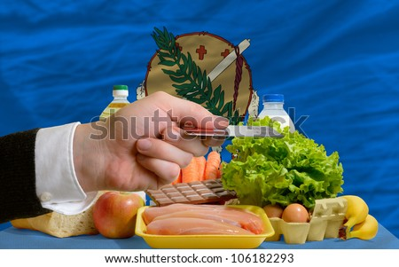 man stretching out credit card to buy food in front of complete wavy american state flag of oklahoma