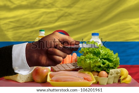 man stretching out credit card to buy food in front of complete wavy national flag of colombia