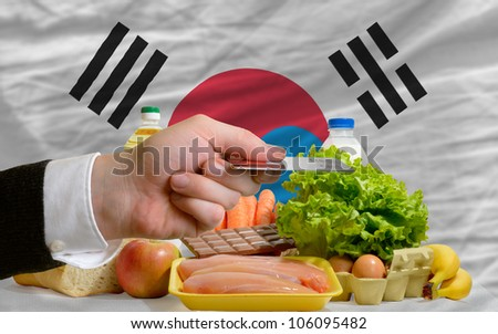 man stretching out credit card to buy food in front of complete wavy national flag of south korea
