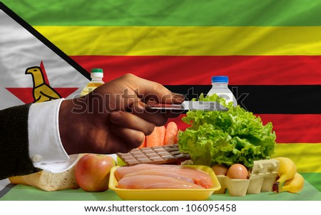 man stretching out credit card to buy food in front of complete wavy national flag of zimbabwe