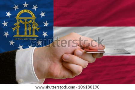 man stretching out credit card to buy goods in front of complete wavy national flag of american state of georgia