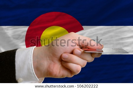 man stretching out credit card to buy goods in front of complete wavy national flag of american state of colorado